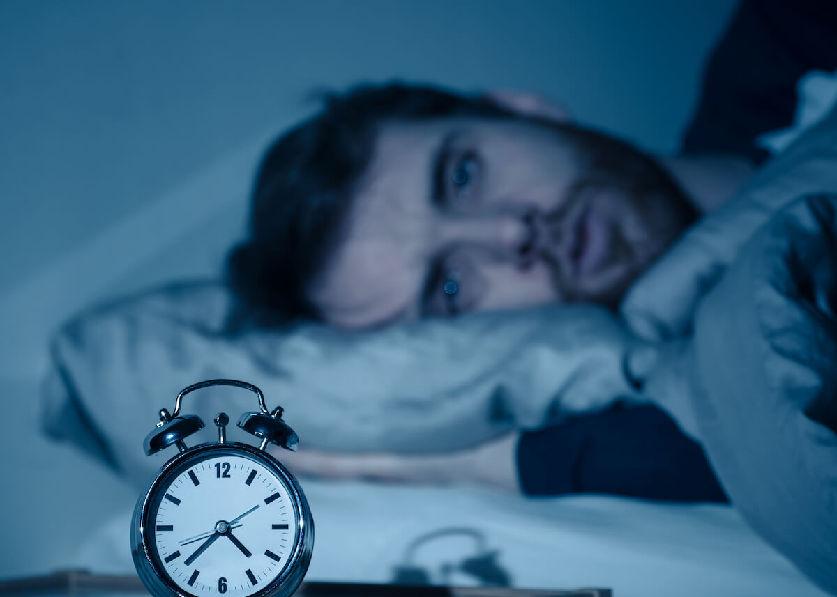 Cortisol and sleep: man laying in bed looking at an alarm clockr