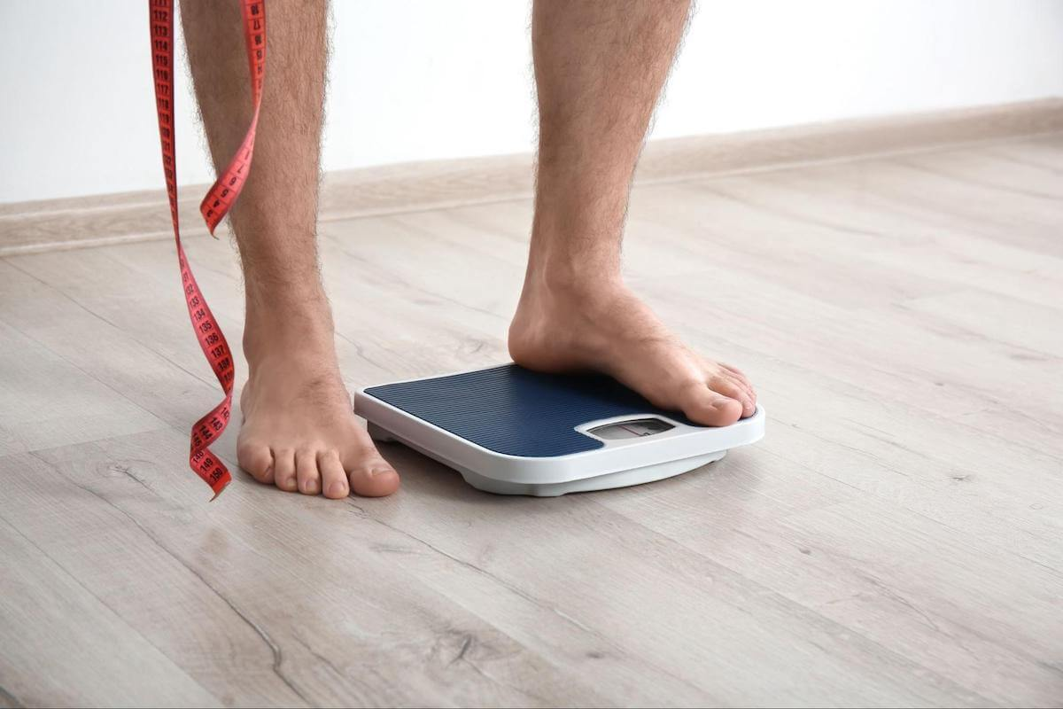 Sleeping after eating: person stepping onto a weighing scale