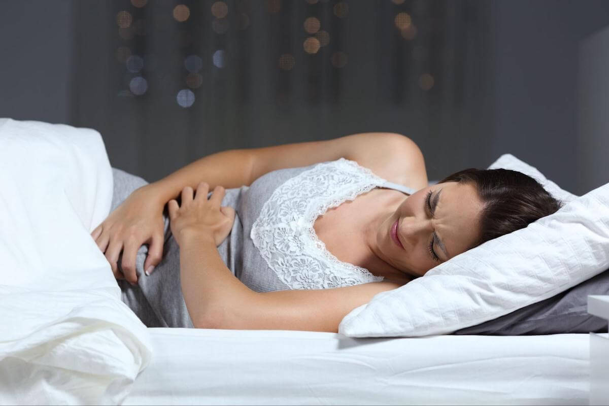 Sleeping after eating: woman with a stomachache laying in bed