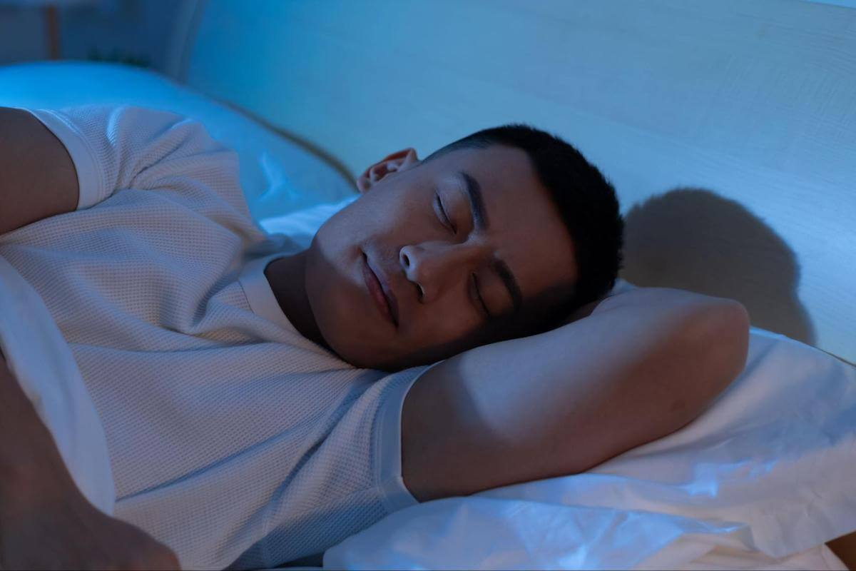 Man sleeping soundly in his bed