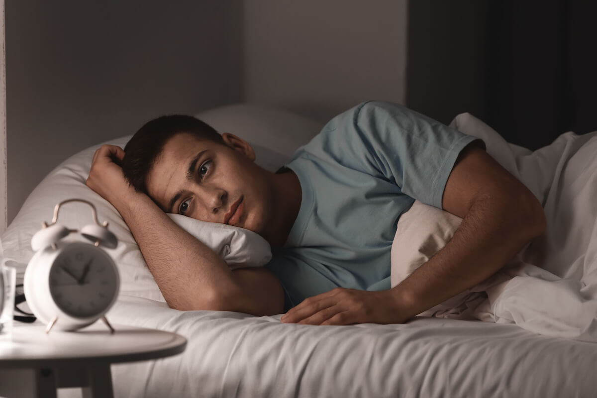 Exercise before bed: person looking at his alarm clock