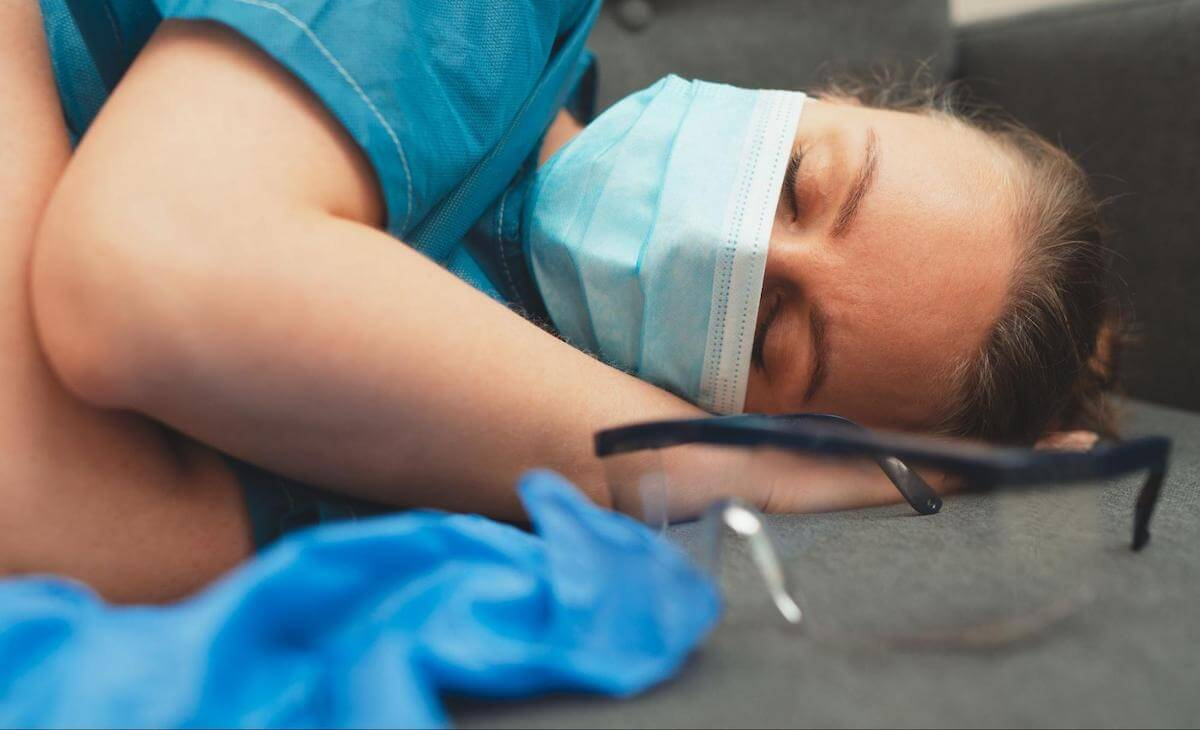 Are naps good for you: medical worker sleeping on the floor with a mask on