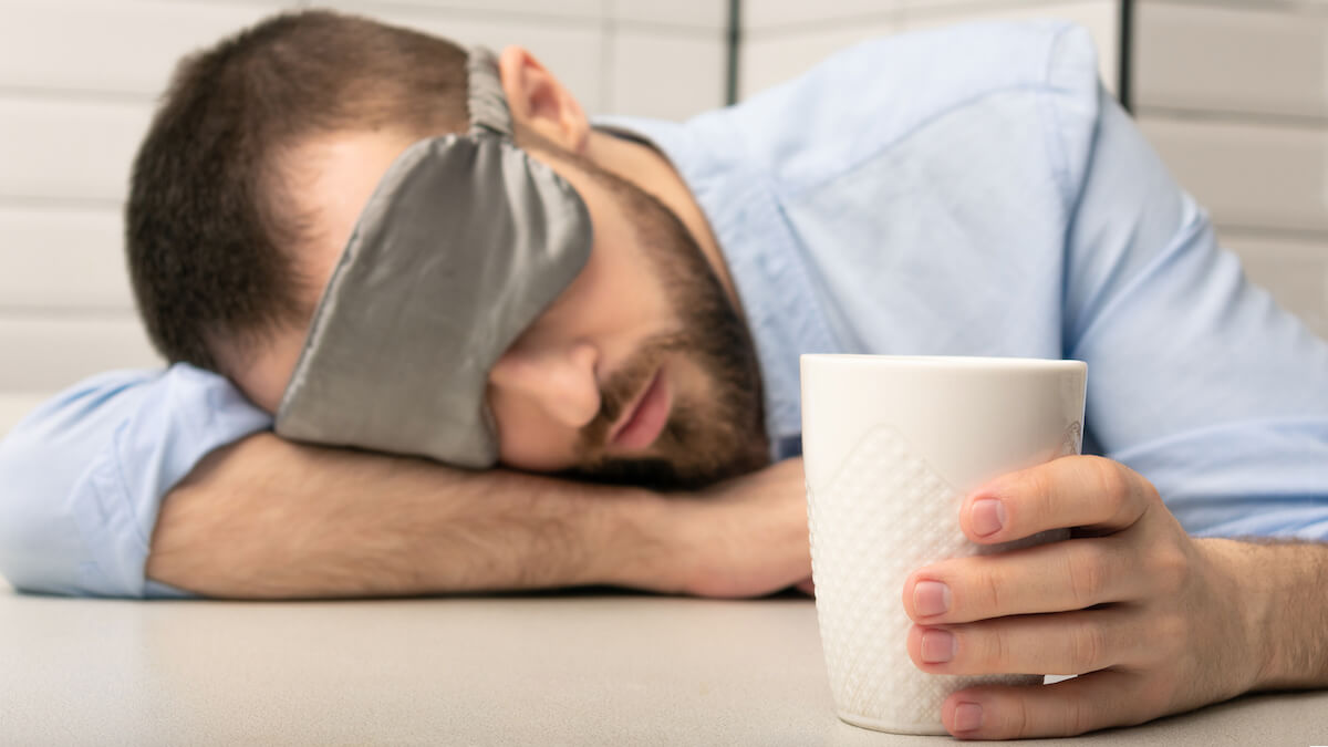 Can't wake up: man wearing an eye mask while holding a cup