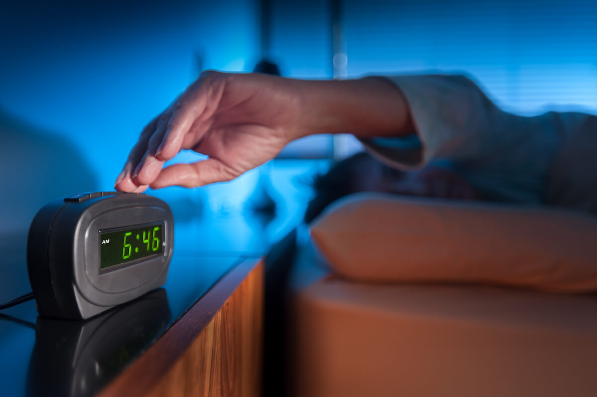 Can't wake up: woman pressing the button of a digital alarm clock