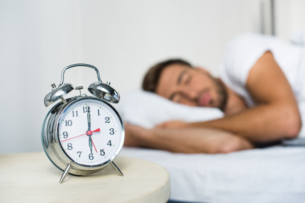 Alarm clock on a bedside table, sleeping man in the background