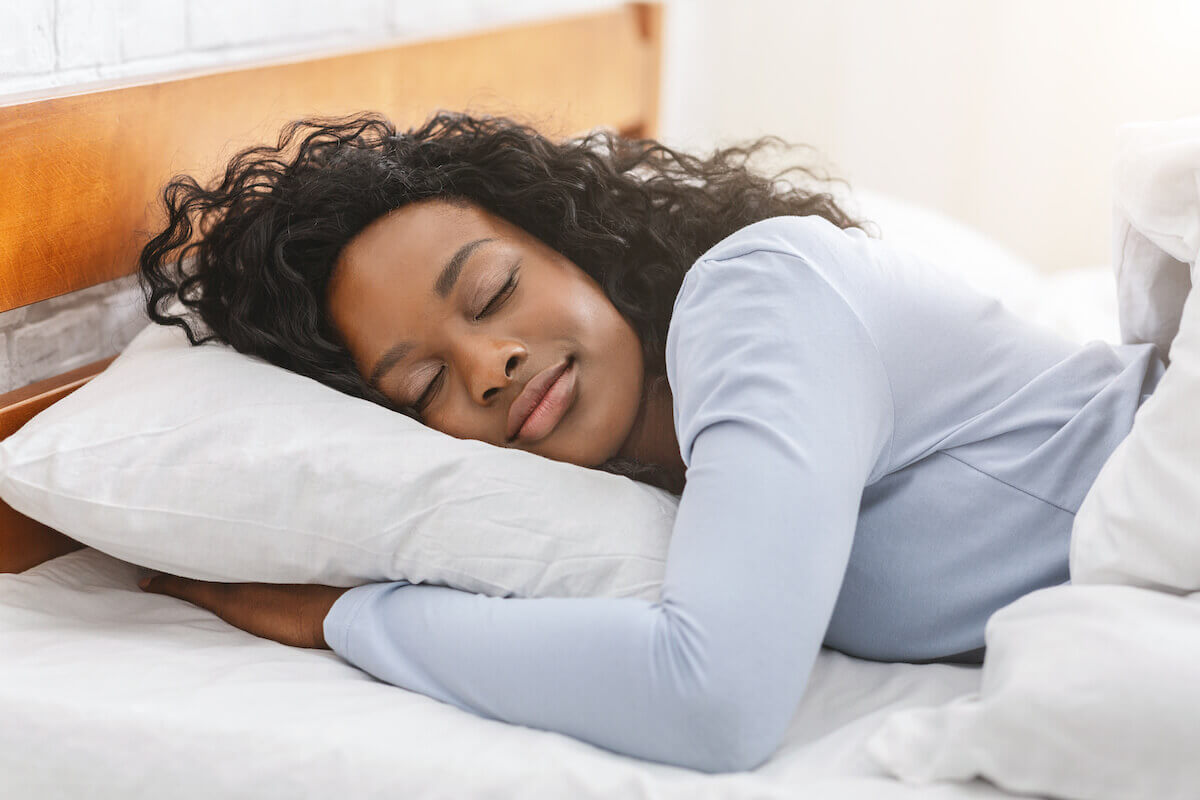 Why am I sleeping so much: A woman sleeps peacefully in bed