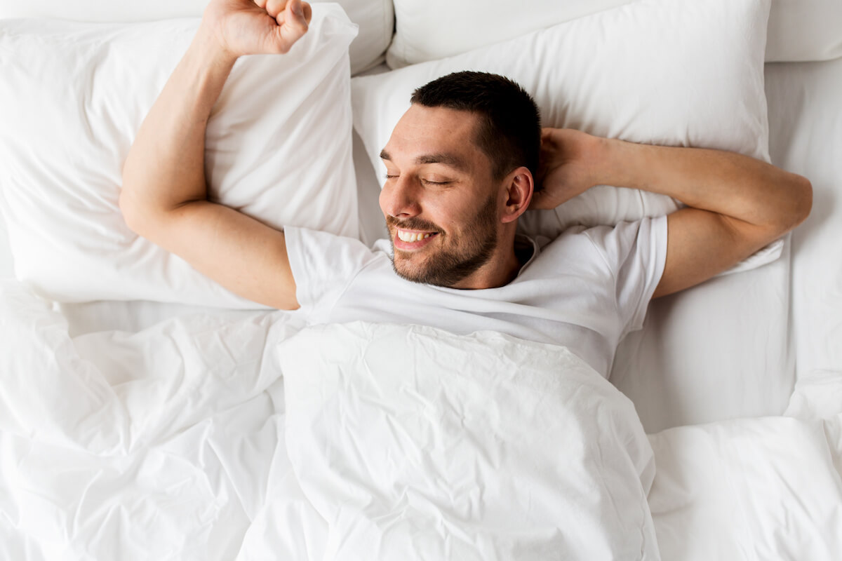 A smiling man stretches as he wakes up