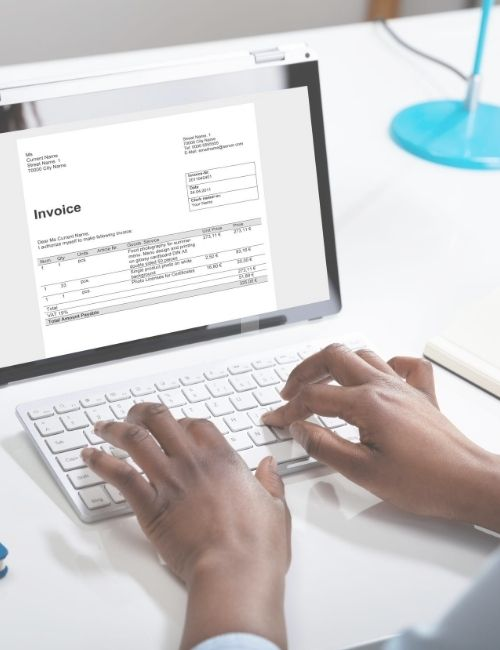 Someone typing on a computer and editing an invoice