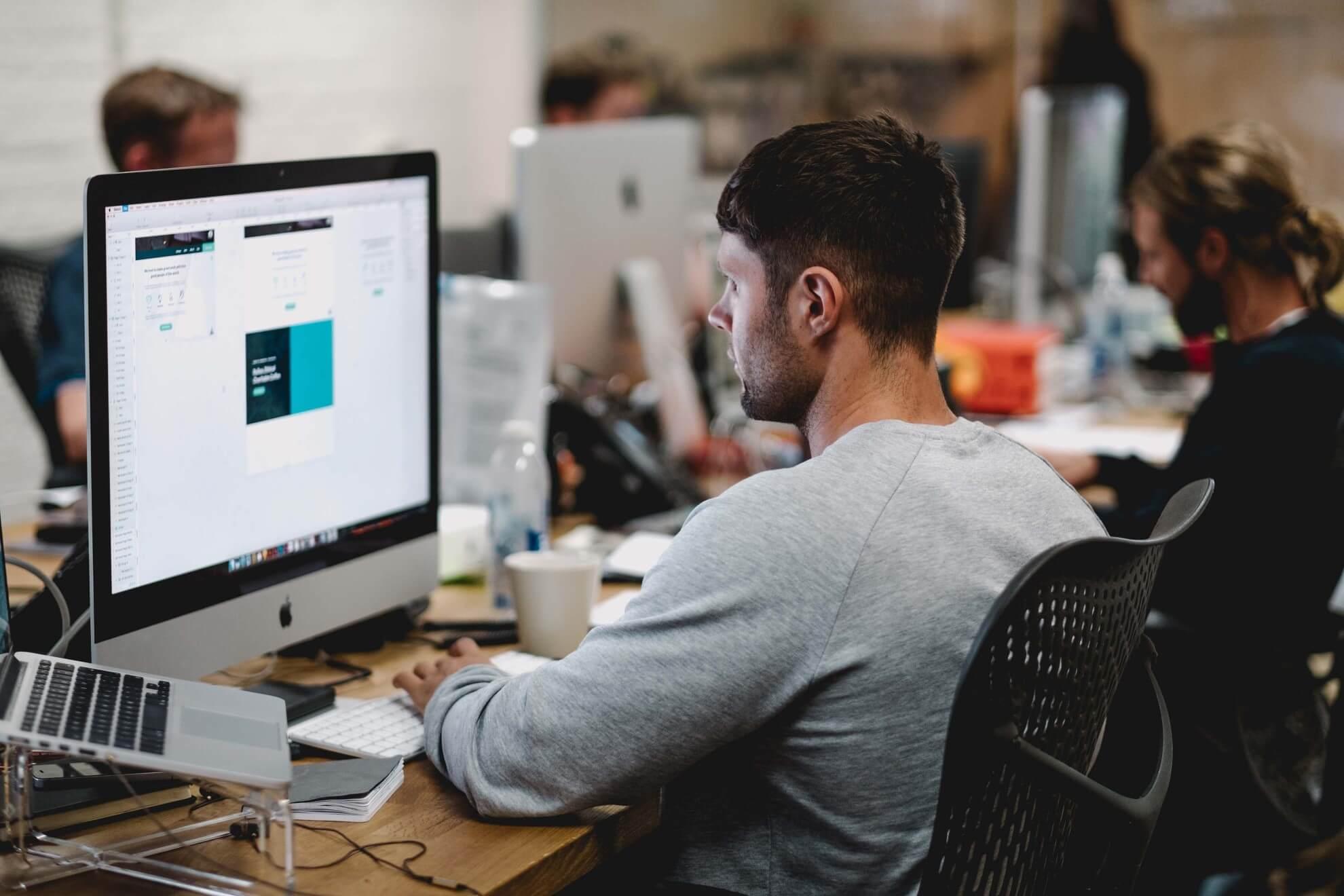Spotzer branding, employee at desk working on computer