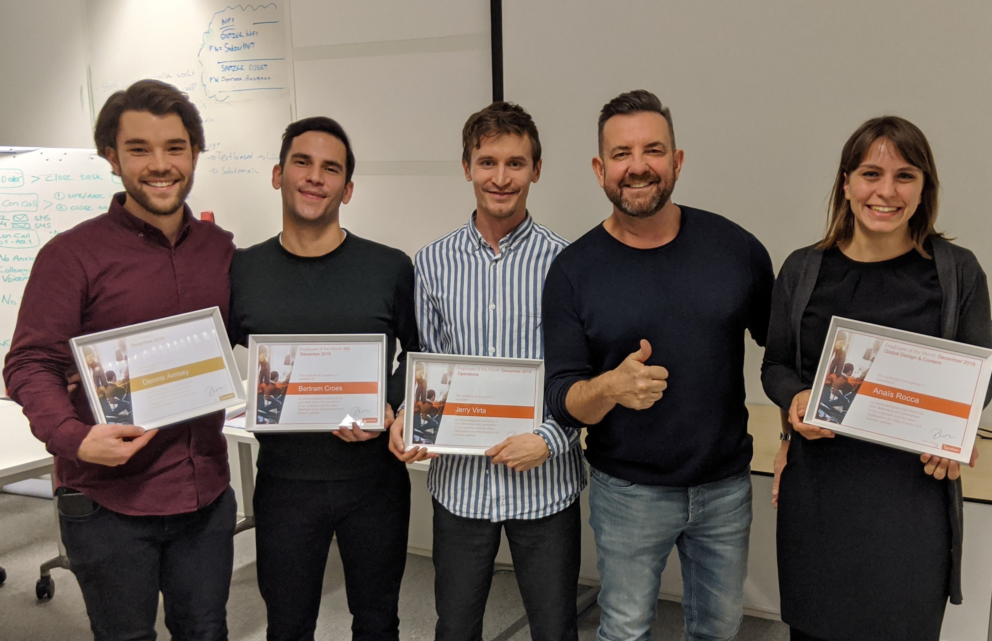 Spotzer employees hold awards at employee of the month event
