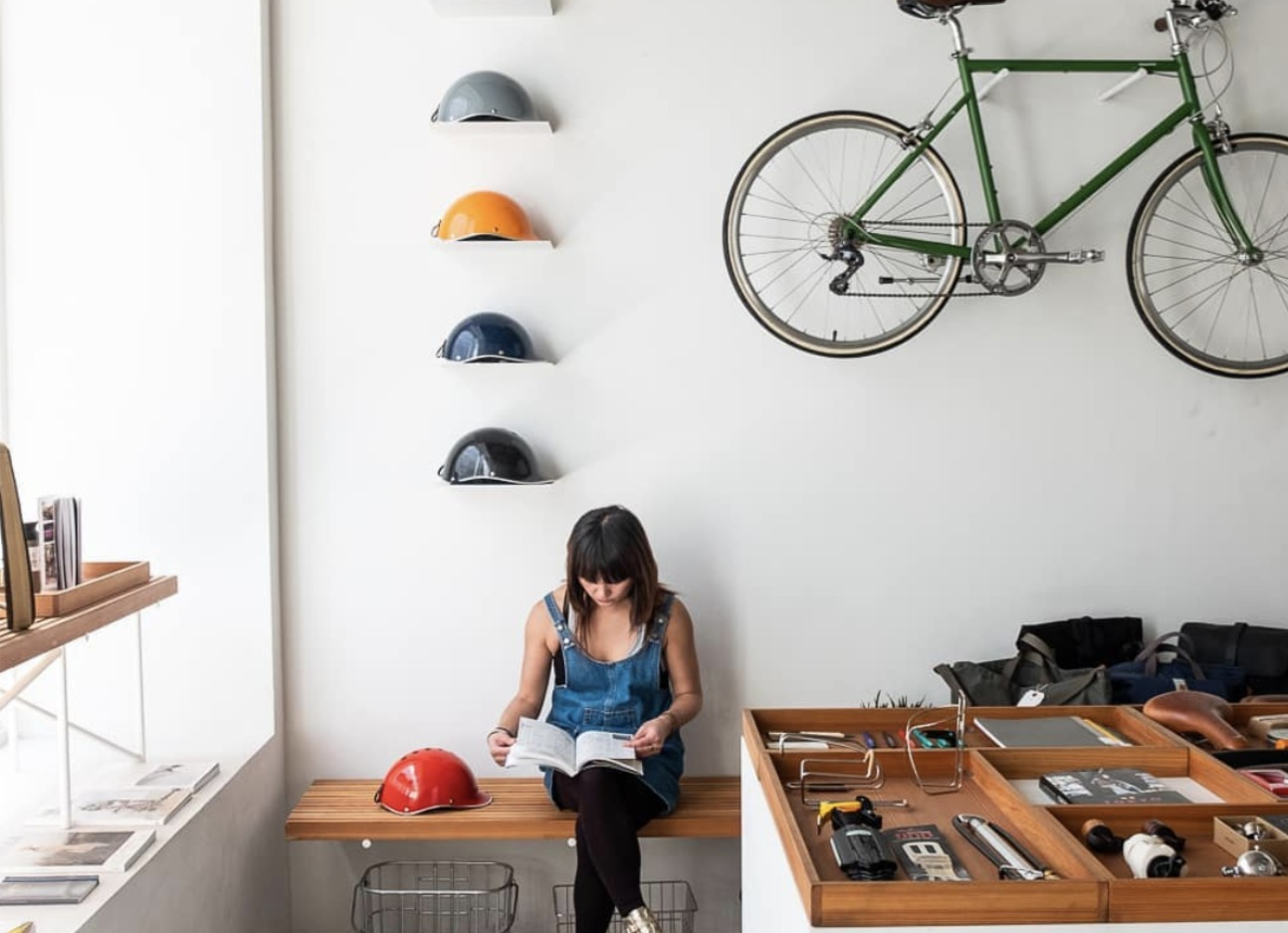 A girl reading a book in a bicycle shop
