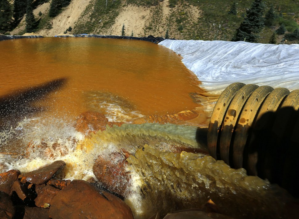 FILE - In this Aug. 14, 2015, file photo, water flows through a series of sediment retention ponds built to reduce heavy metal and chemical contaminants from the Gold King Mine outside Silverton, Colo. The U.S. government settled a lawsuit Wednesday, Aug. 5, 2020, brought by the state of Utah over a mine waste spill caused by federal workers that sent wastewater downstream to several states from the inactive Gold King Mine in southwestern Colorado five years ago. The Environmental Protection Agency agreed to fund $3 million in Utah clean water projects and give another $360 million to the state for remediation projects at abandoned mine sites. (AP Photo/Brennan Linsley, File)