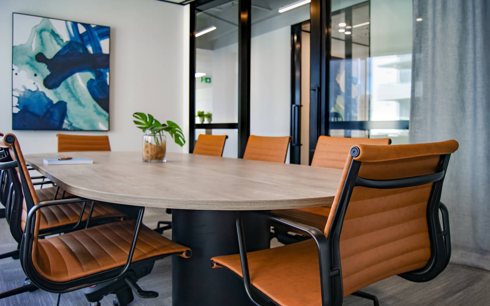 Office conference room setting with wood table, orange chairs, and a plant