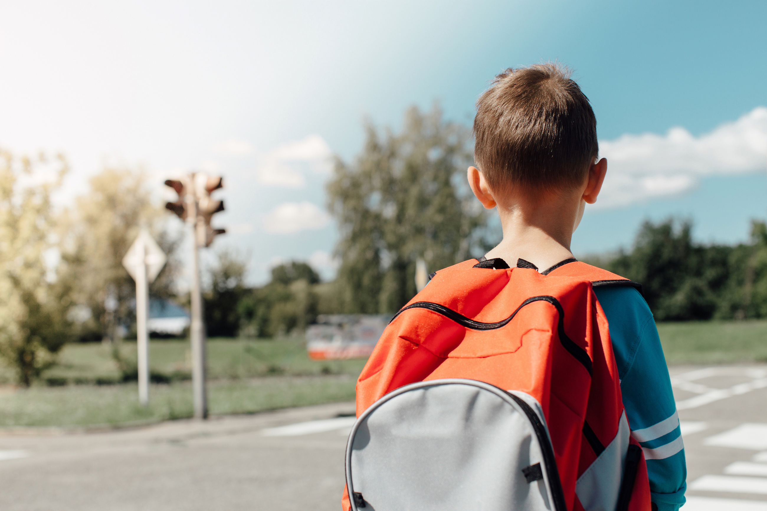 Eine Junge alleine auf dem Schulweg.
