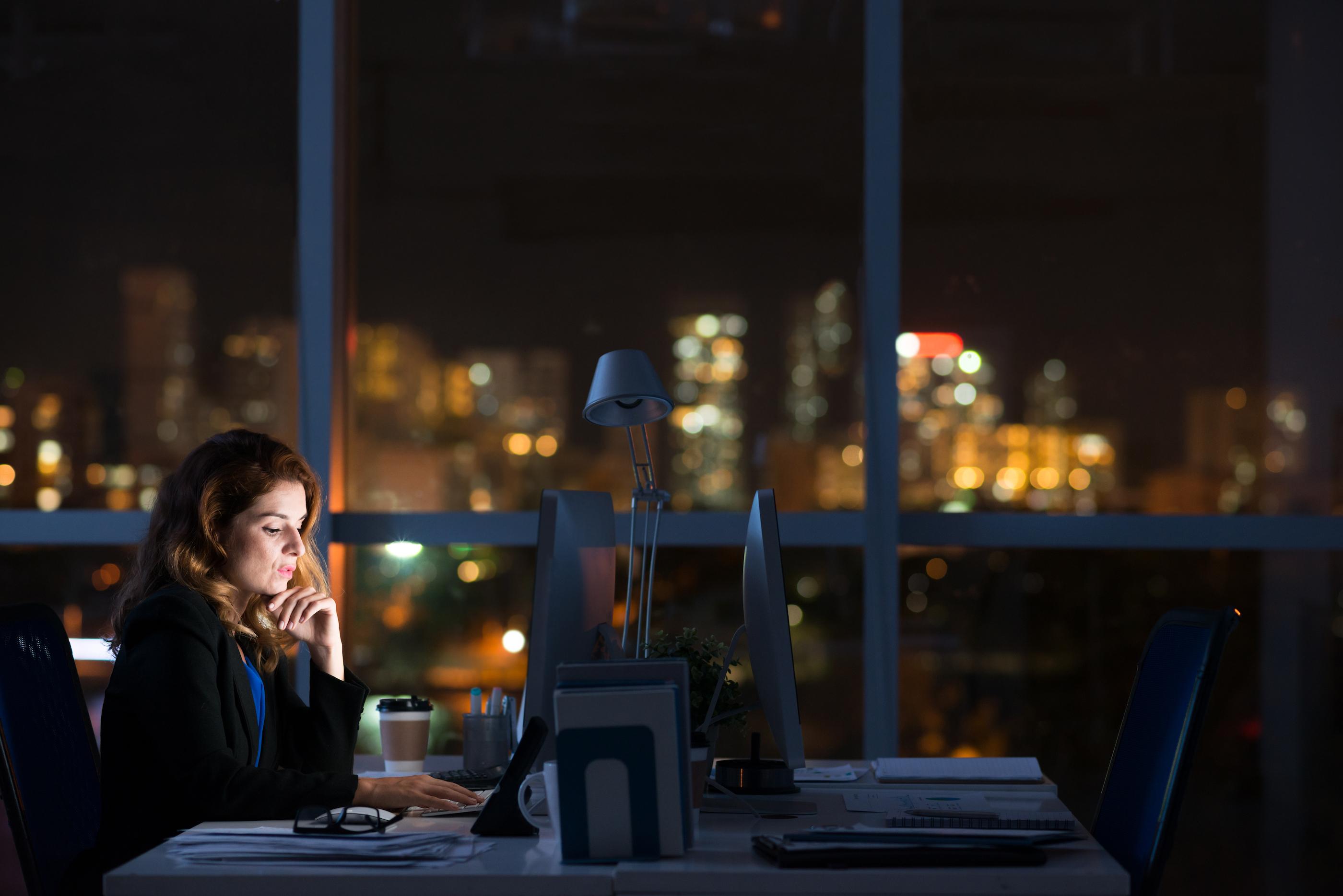 Eine Frau, die im dunklen alleine im Büro sitzt und arbeitet.
