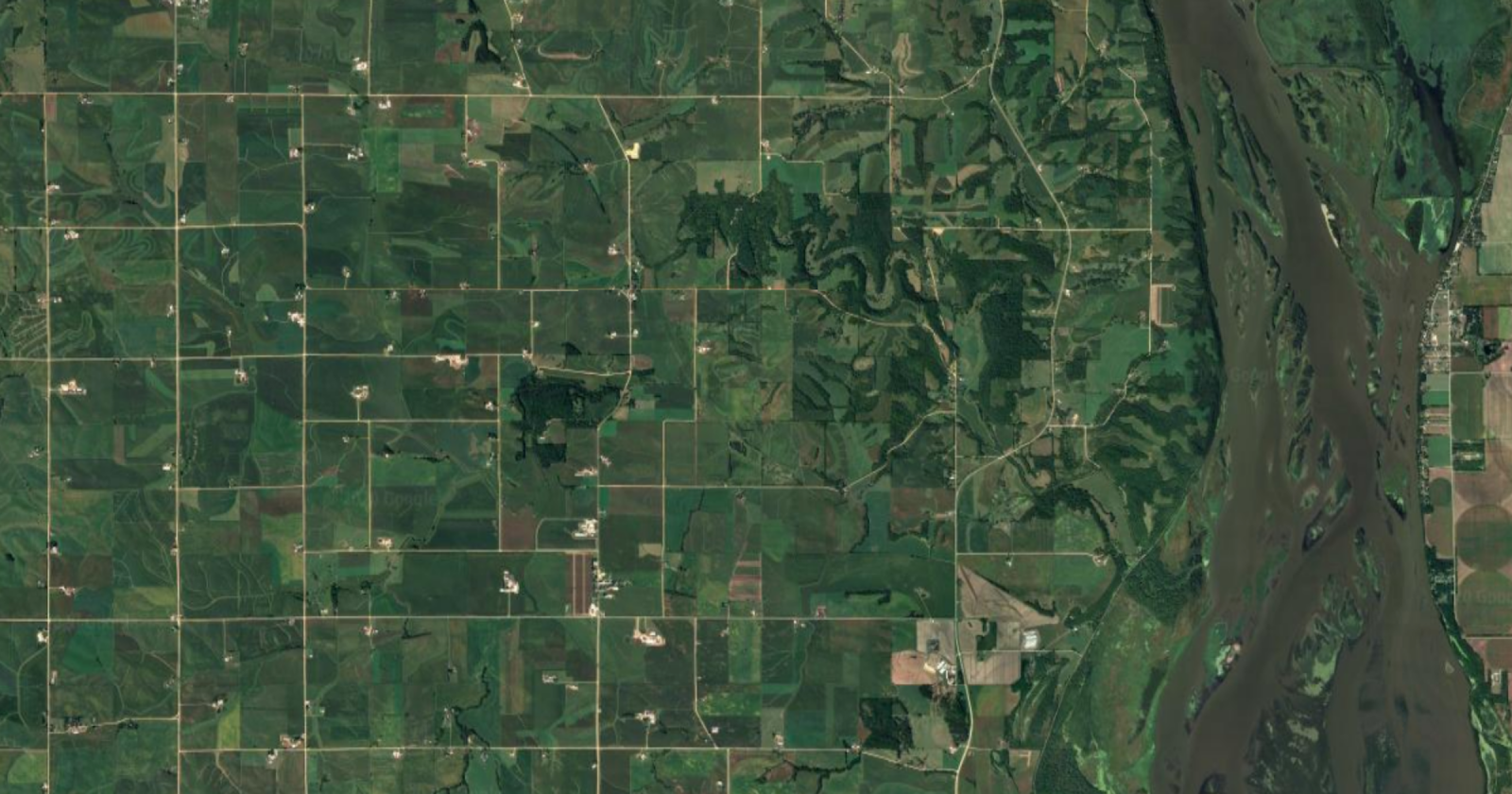 An arial view of some green pastures, mountains, rivers, and roads.