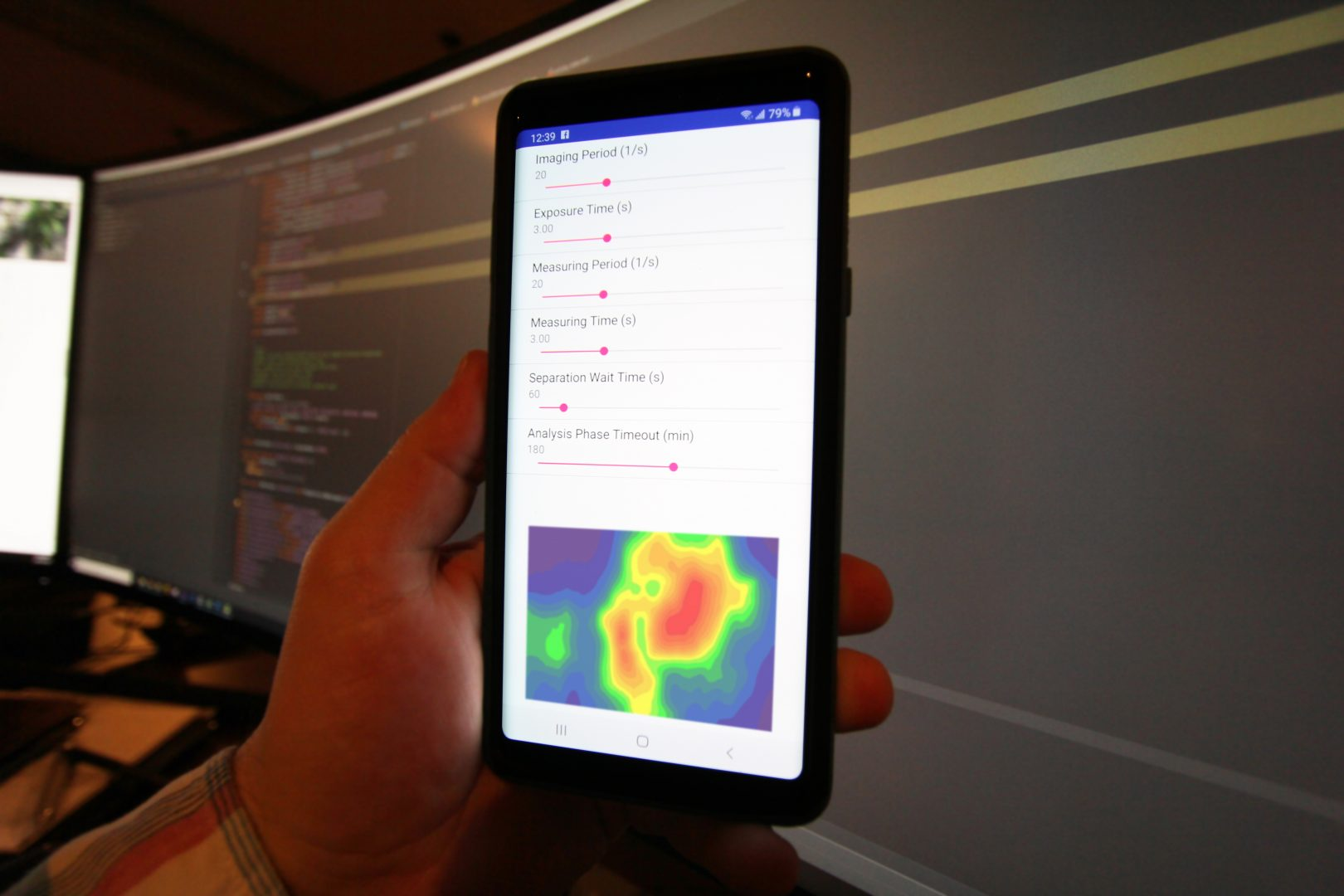 A hand holding a mobile phone with the Verv app running showing a heatmap