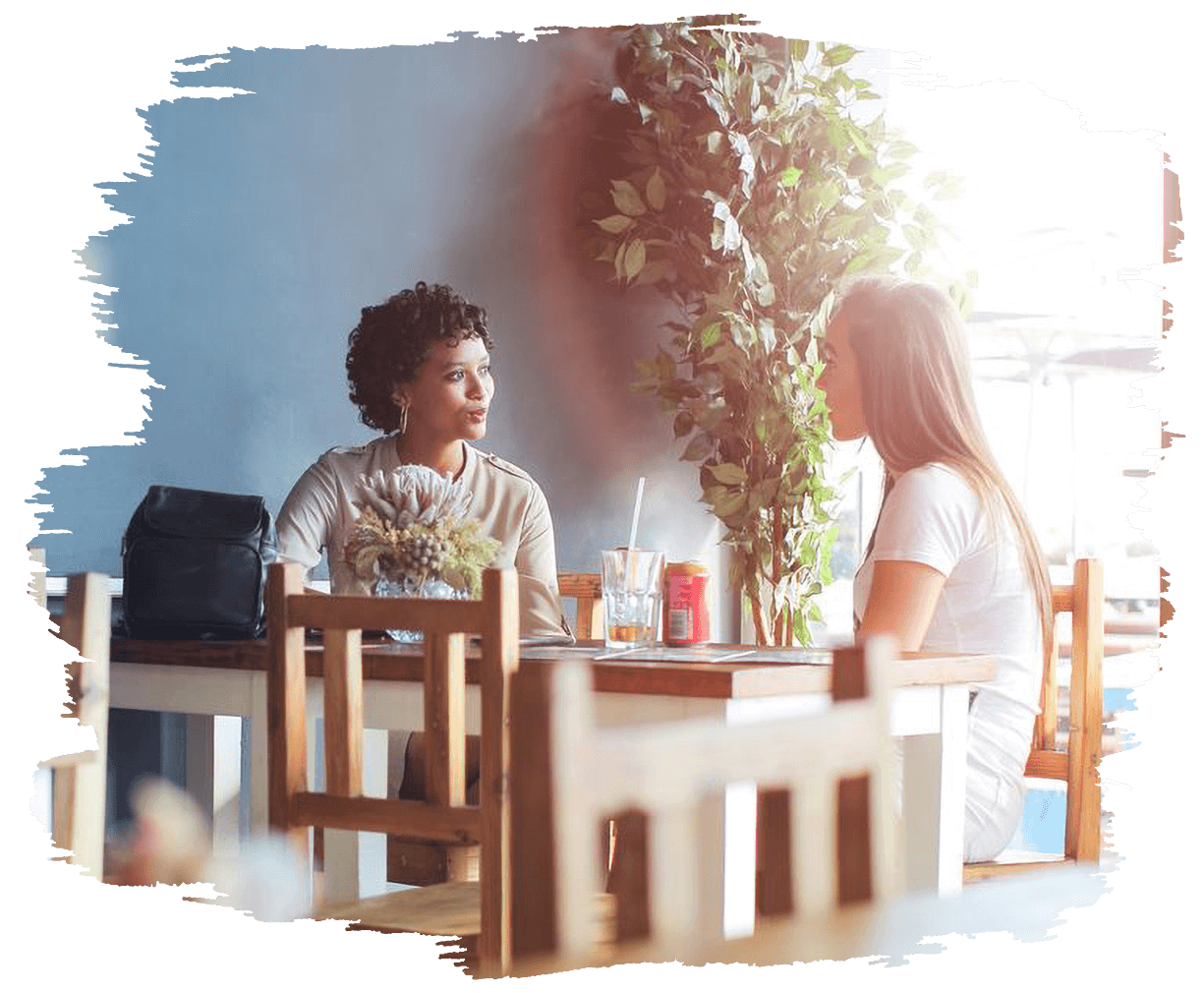 This is an image of two woman in a cafe with the sun shining in the background