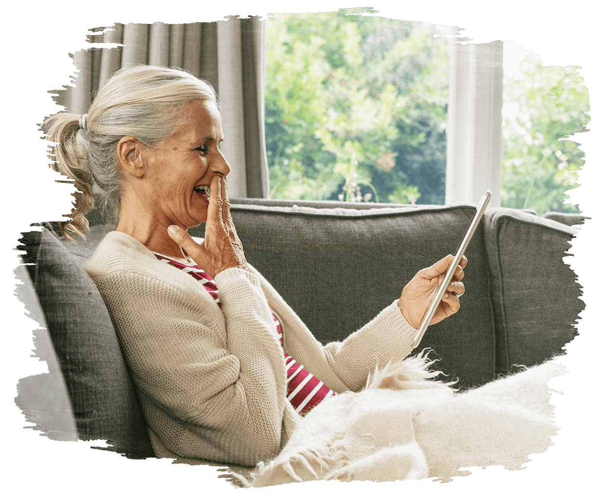 This is an image of a elderly woman  lying on the couch looking a an iPad