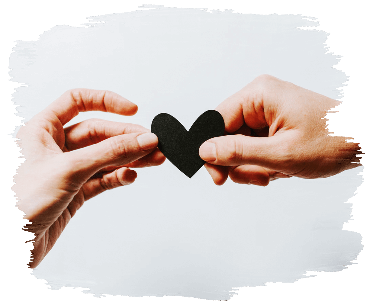 This is an image of a small black heart being held by two hands