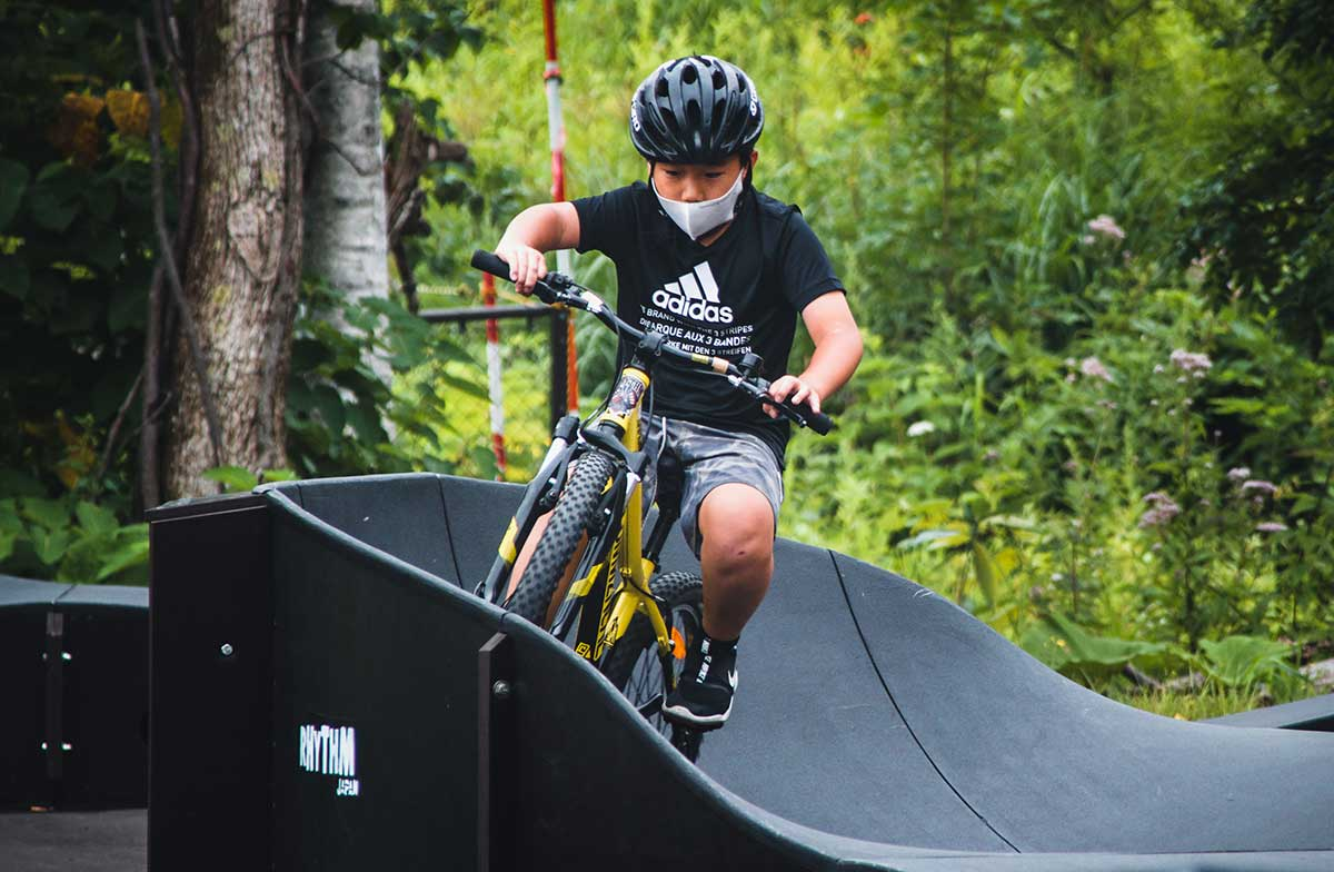 Young child cycling on pump track during summer kids camp