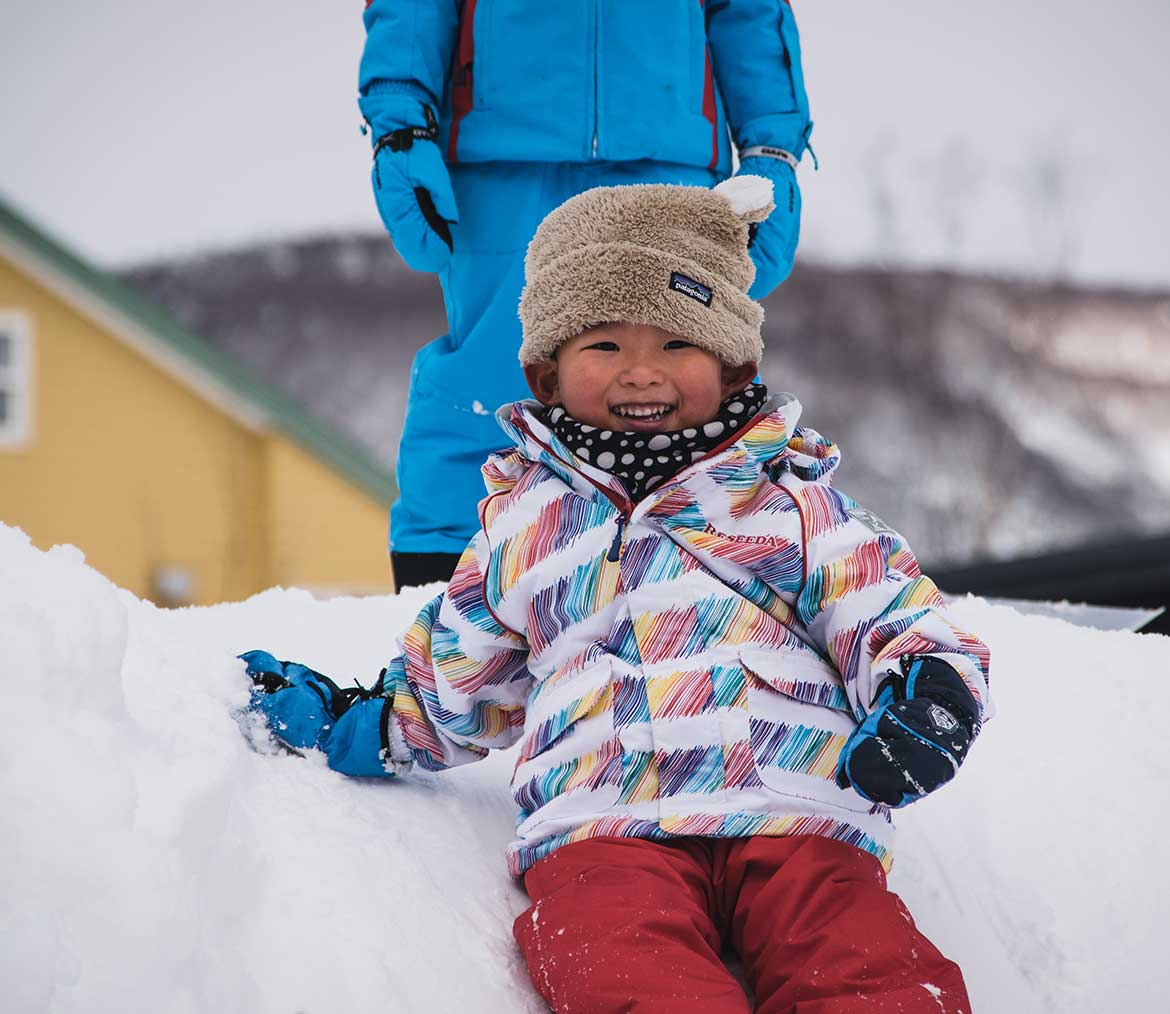 Young child sliding down snow hill
