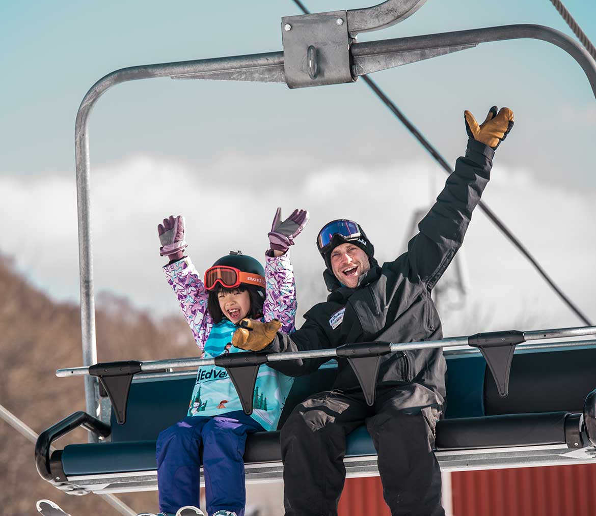 Young skier with instructor on chair lift