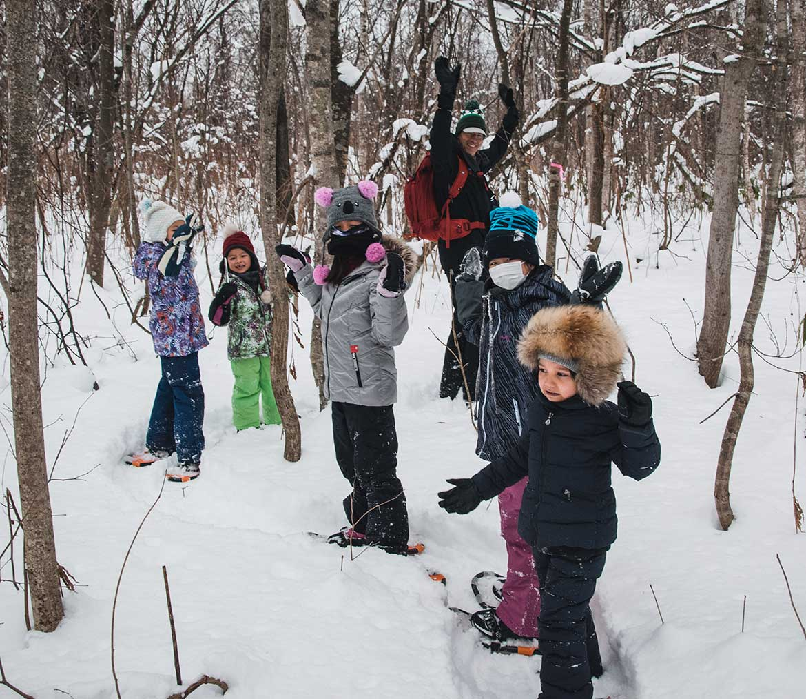 Group of children on a snowshoe tour with camp mentor