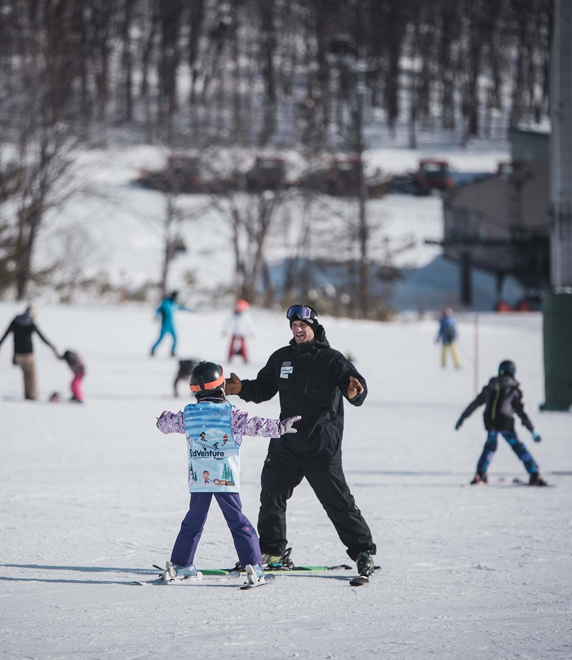 Ski instructor out on the slopes teaching young child how to ski