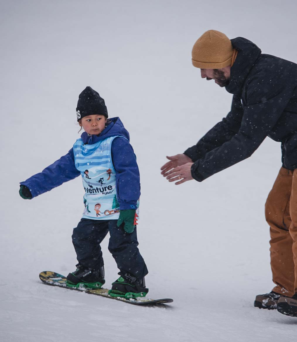 Snowboard instructors teaching young child how to snowboard