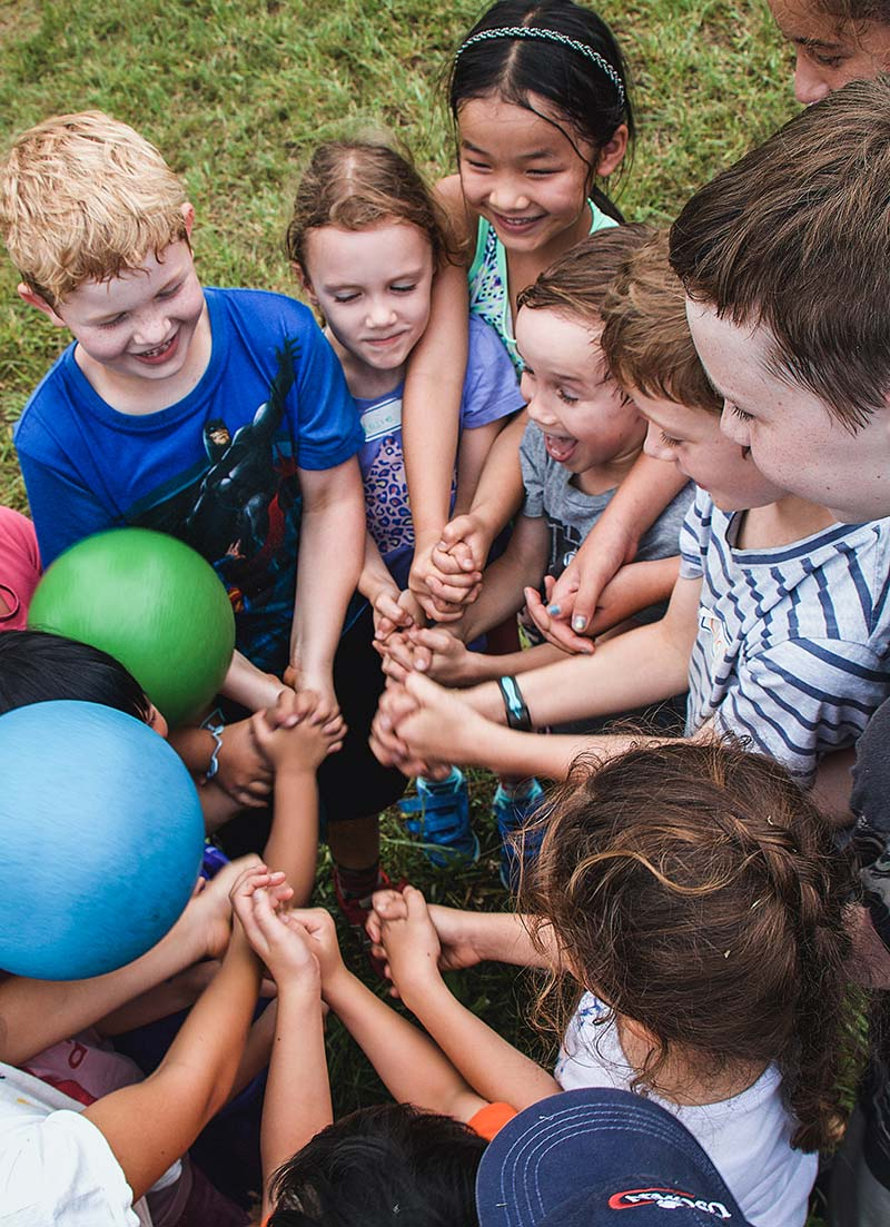 Group of children together with their hands in the middle of a circle
