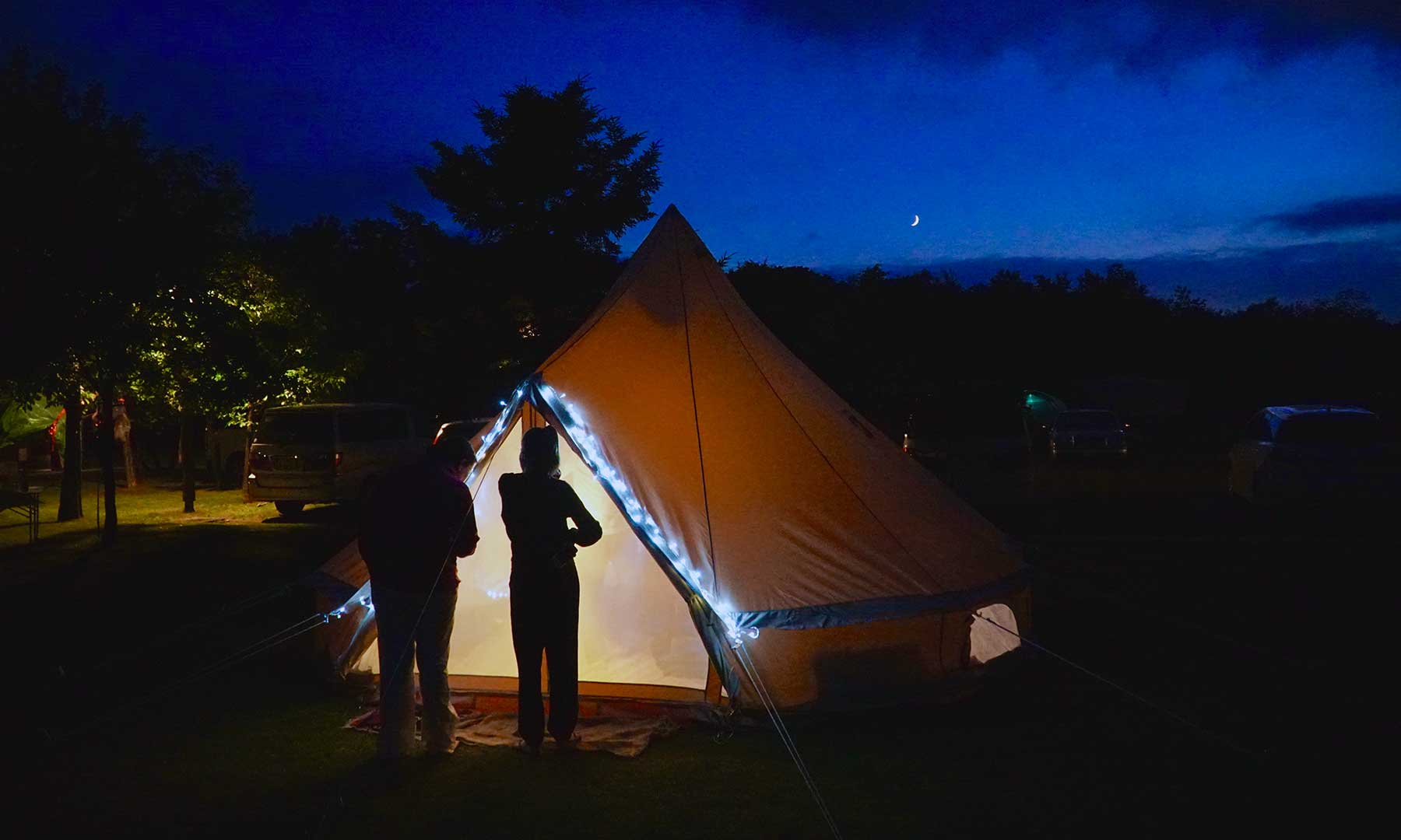 Silhouette of two people standing in front of camping tent at dusk