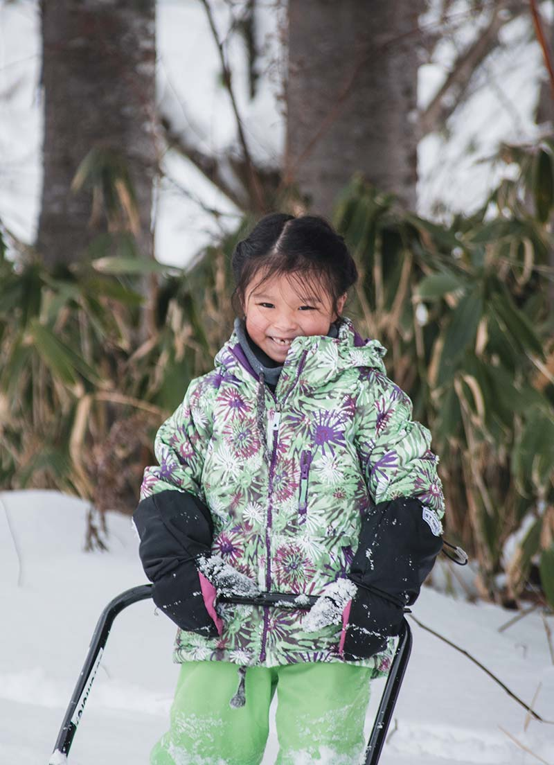 Young child playing in snow at winter camp