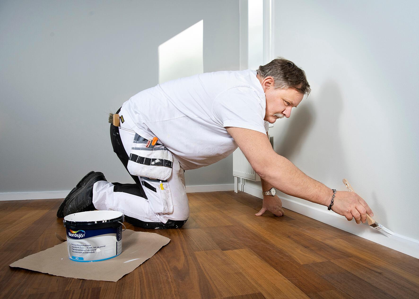 Målar vägg och golvlist med vit färg