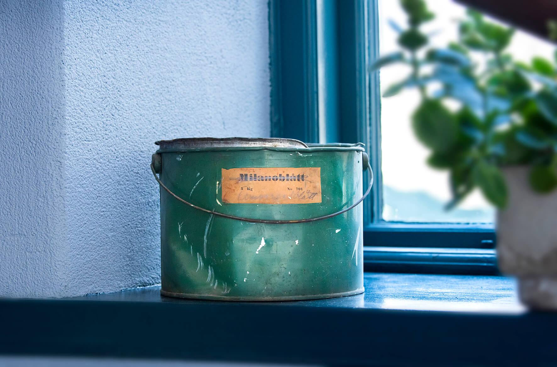 Målarburk med gediget material i gammalt fönster