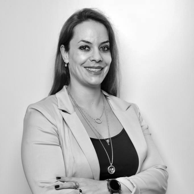 Foto de perfil Milena Hidalgo. Na foto se vê uma mulher de braços cruzados e sorriso no rosto.