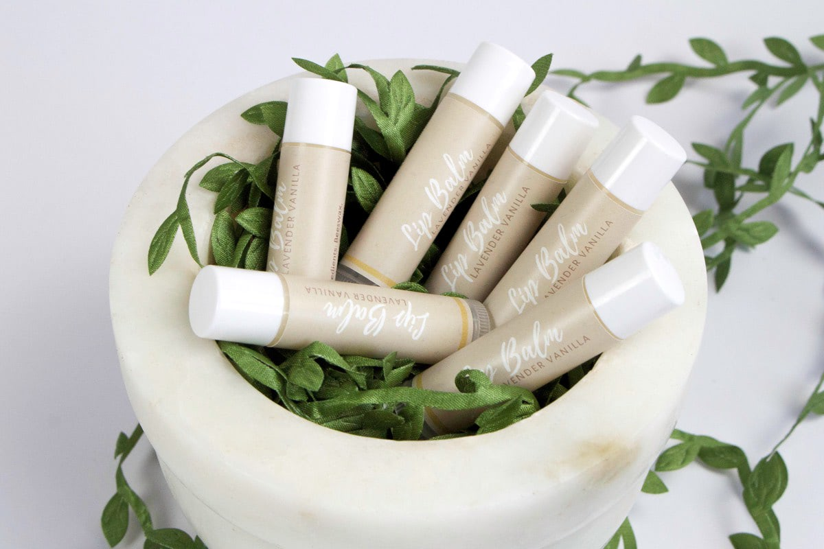 picture of six lip balms in a ceramic bowl covered in leaves