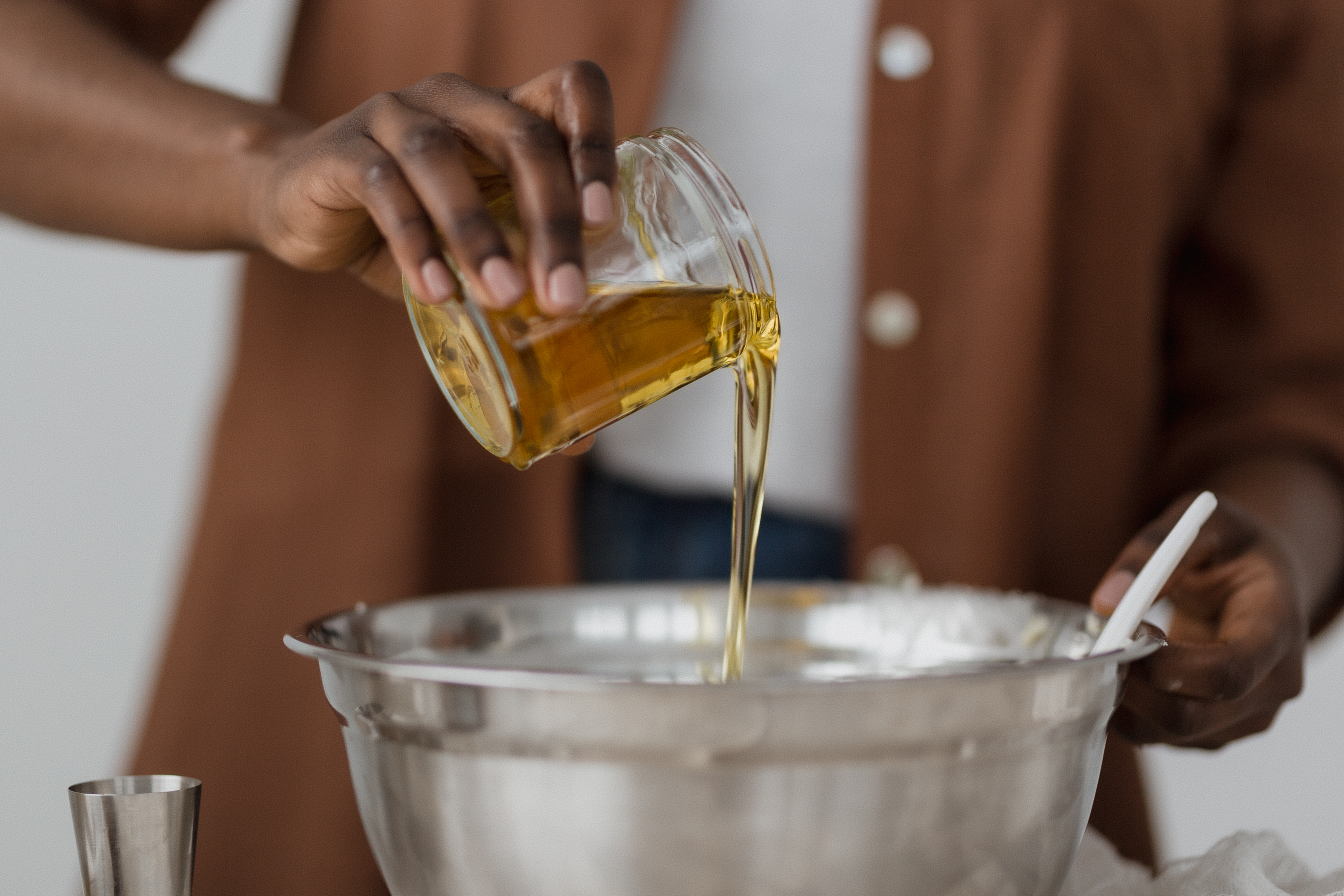 a glass jar filled with olive oil being poured into a stainless steel bowl