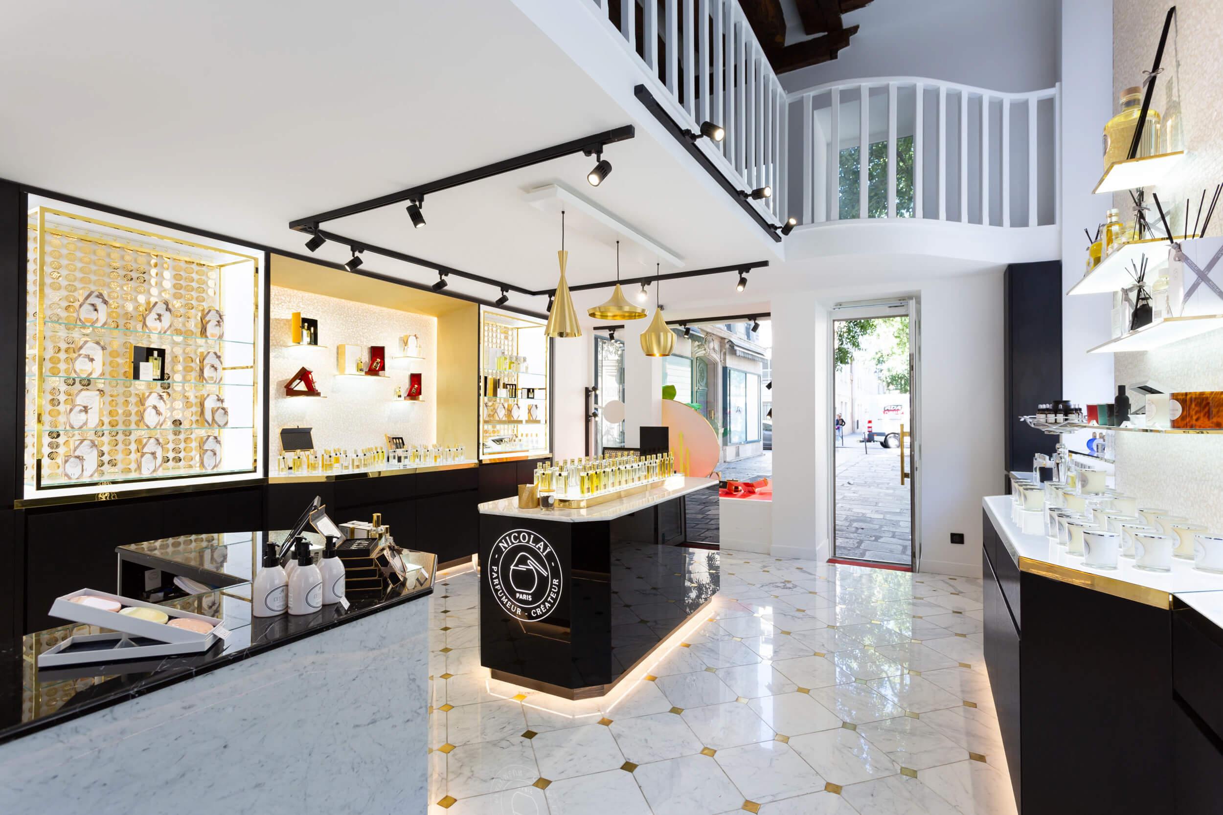 Vue d'intérieur de la boutique Nicolaï rénovée par Heliot dans les tons dorés, blancs et noirs et îlot central mettant en valeur les parfums