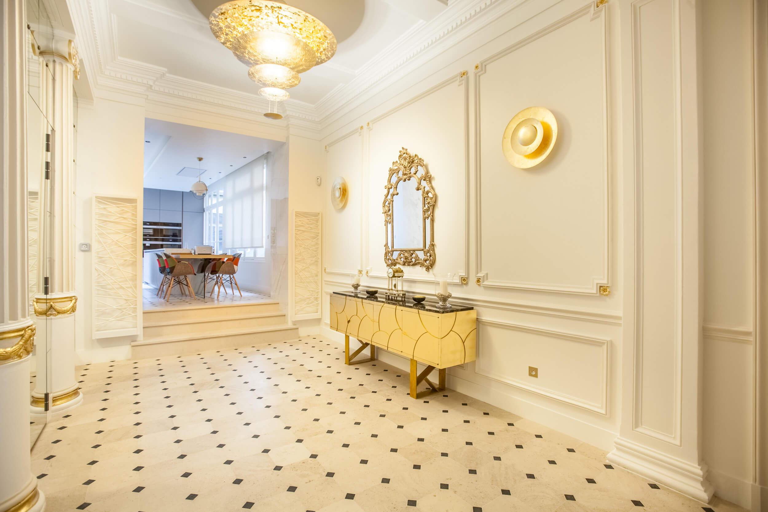 Entrée de l'appartement du huitième arrondissement de Paris, décoration dans les tons blancs et dorés, aménagé par Heliot