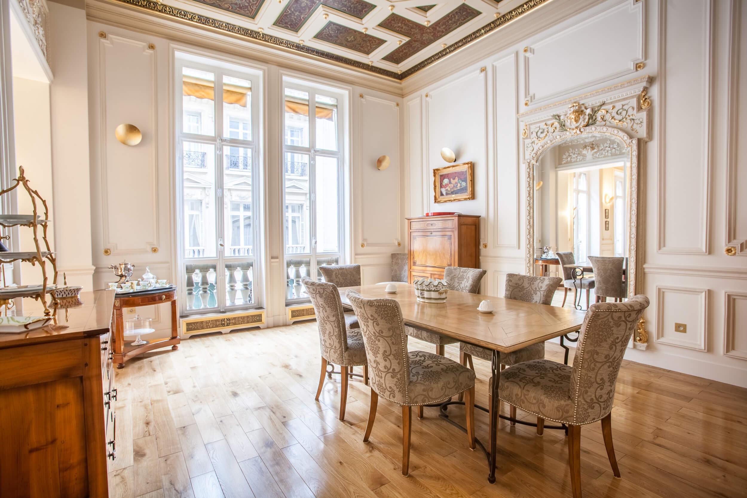 Salle à manger de l'appartement du huitième arrondissement de Paris, décoration dans les tons blancs et dorés, aménagé par Heliot