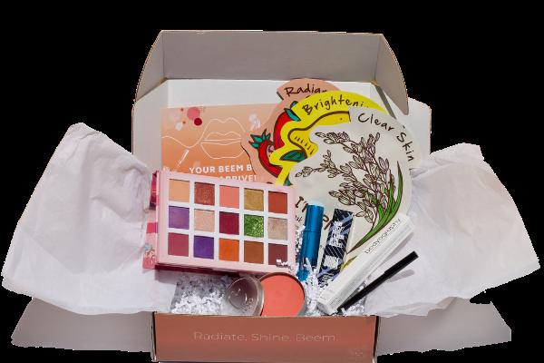 Open Beem Box with eyeshadow, Uoma Beauty lipgloss, Tony Moly mask, Cargo cosmetics blush, and bodyography eye pencil.