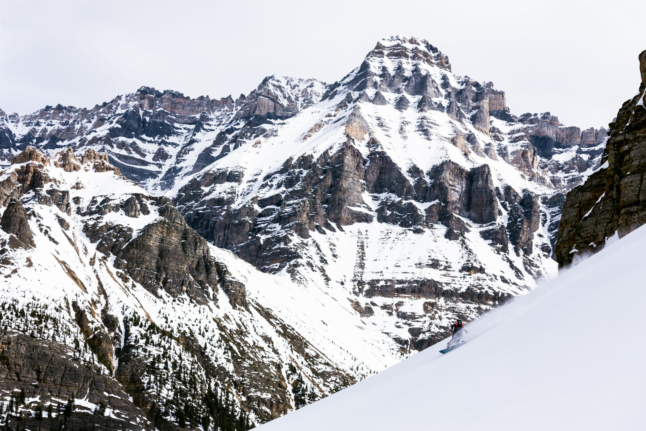 Man snowboarding down steep slope with mountains in the background.