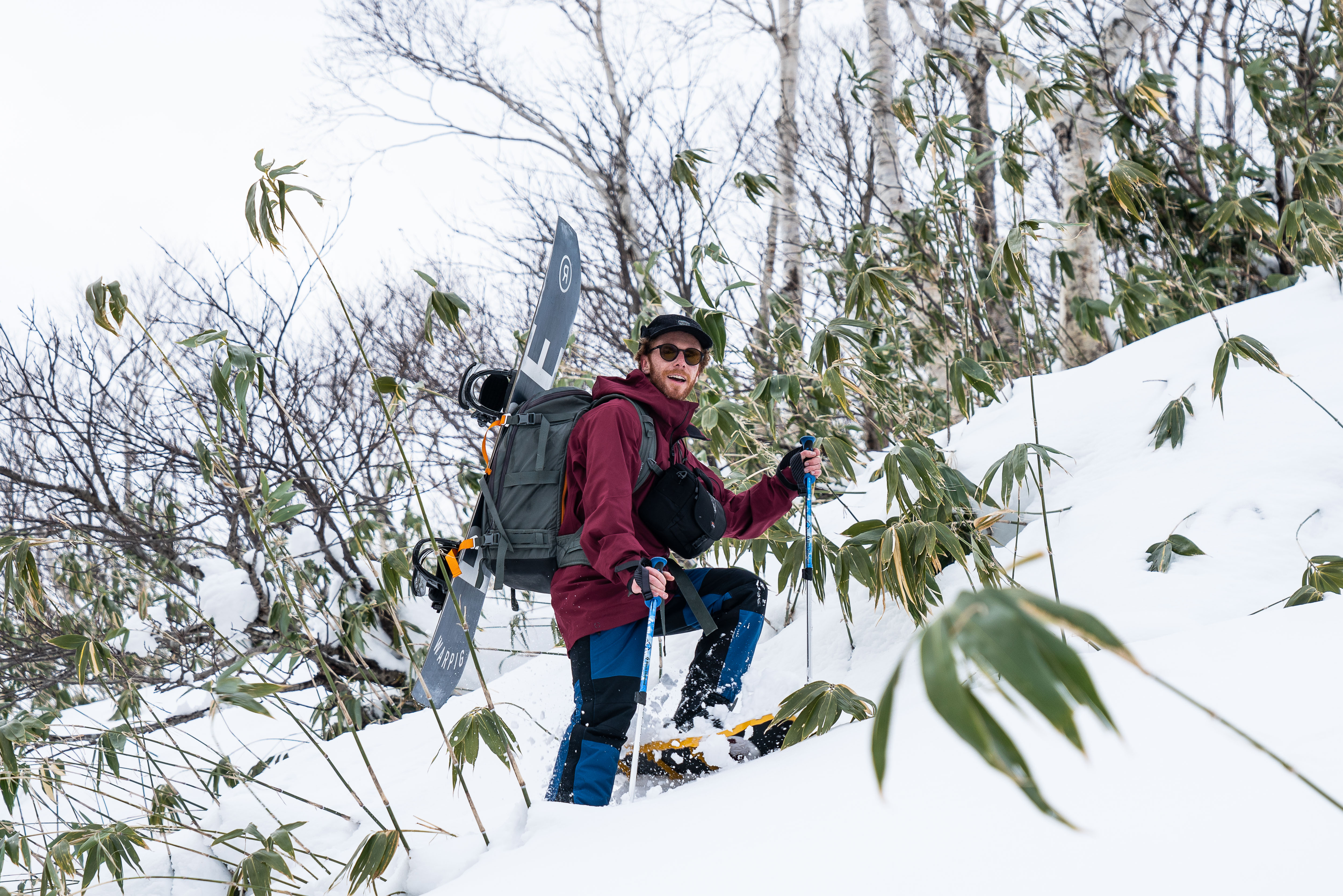 Man snowshoeing up snowy slope.