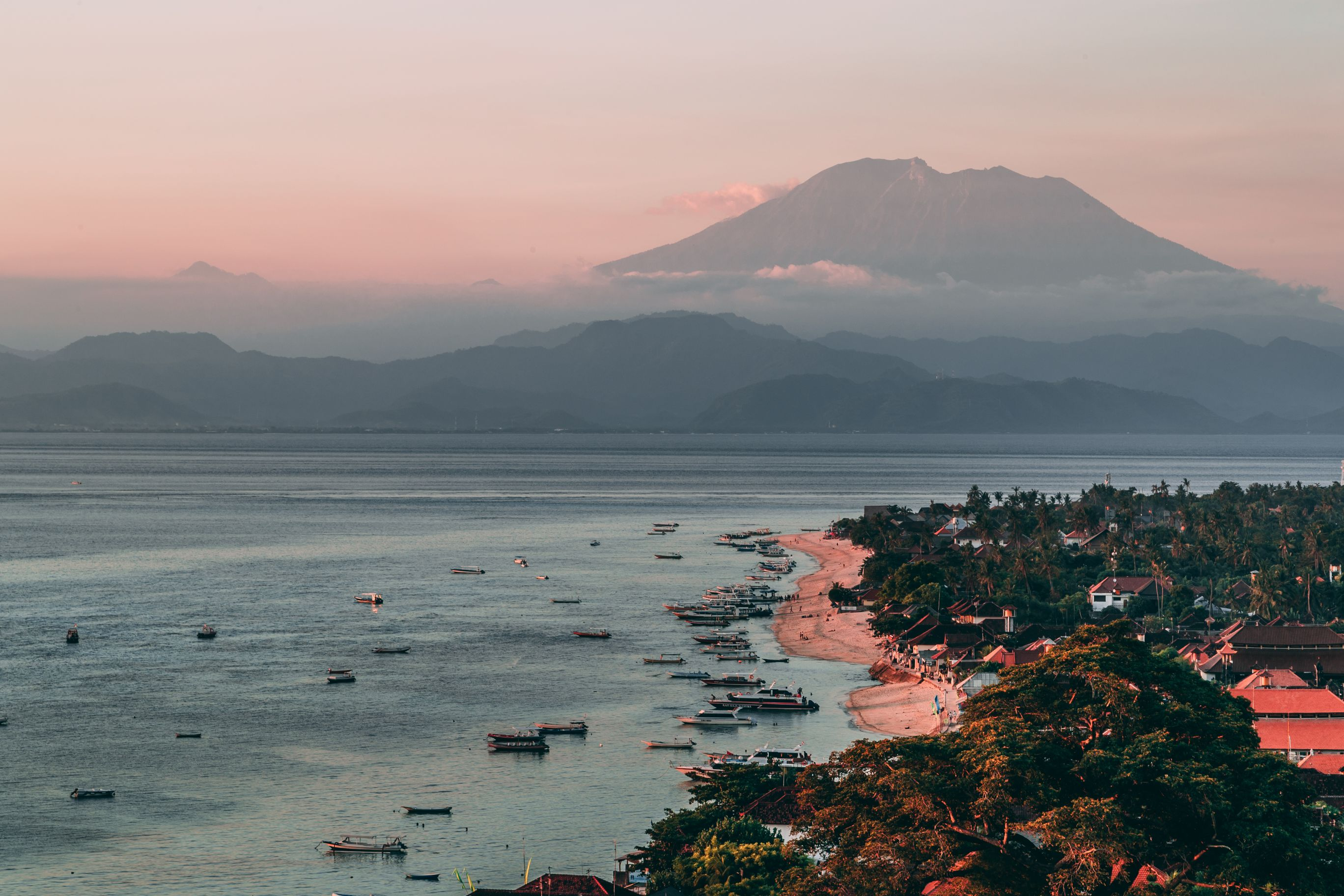Sunset over a balinese beach, village and fishing boats.