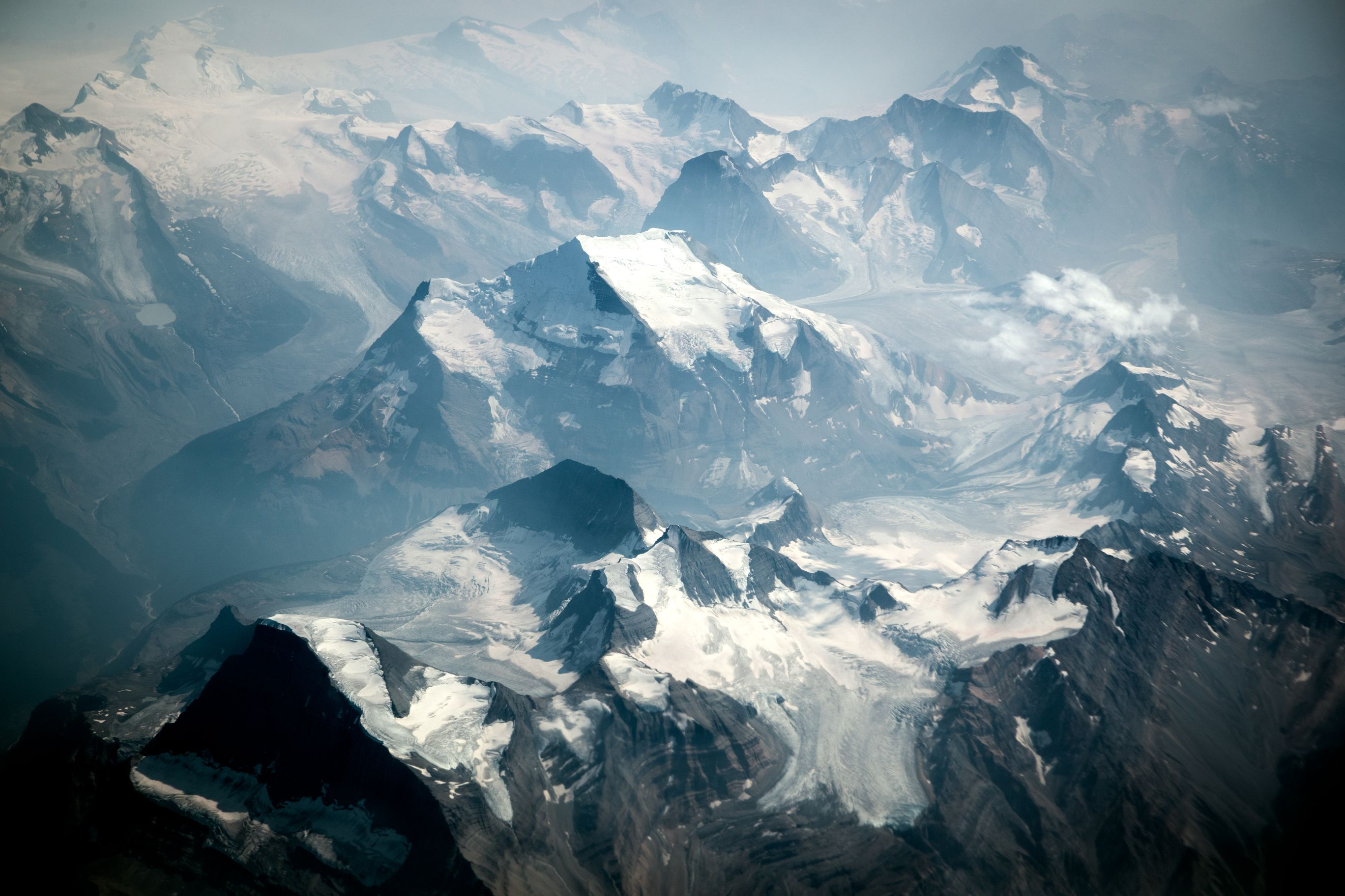 Aerial shot of rocky and snowy mountain peaks.