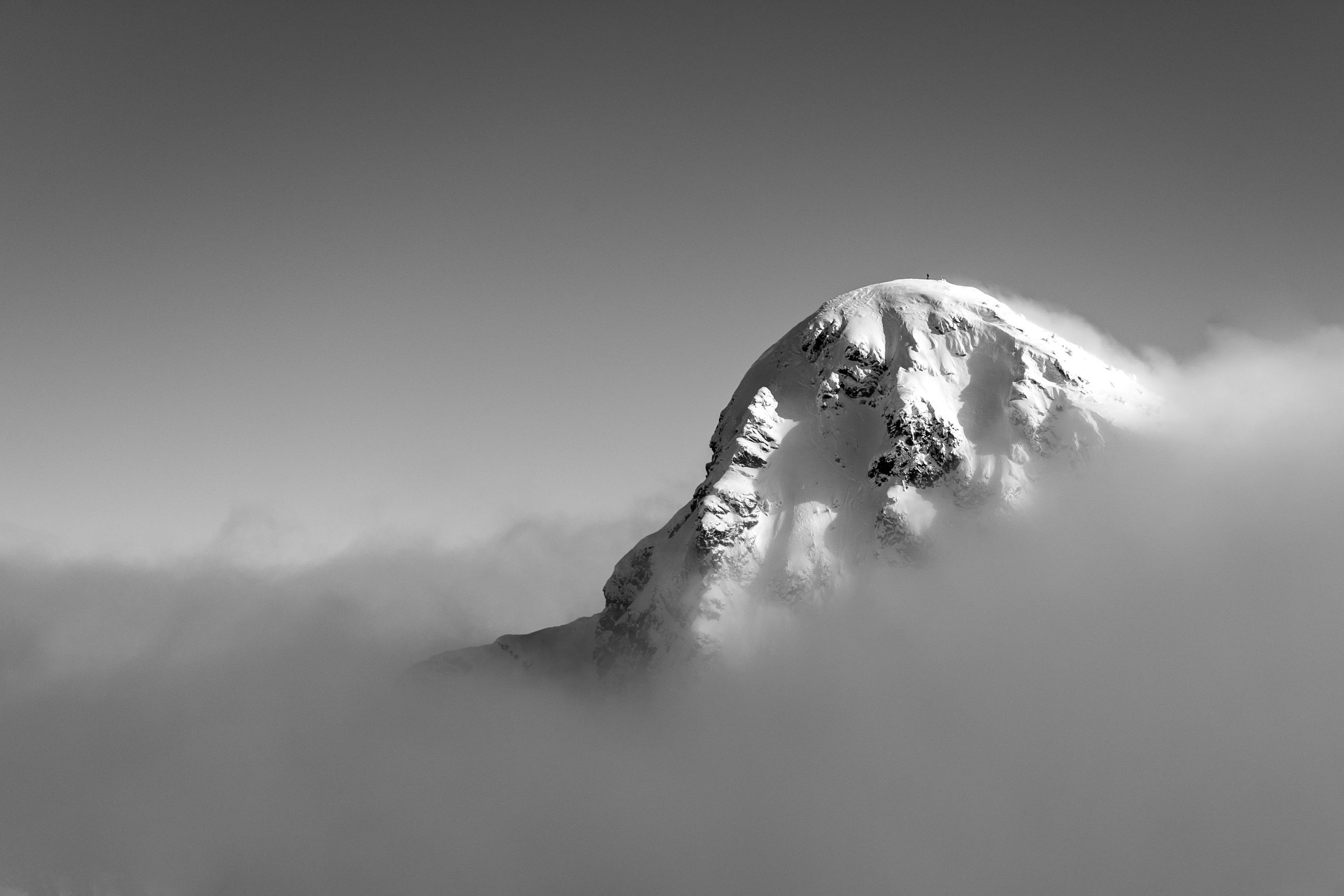 Black and white mountain peak above the clouds.