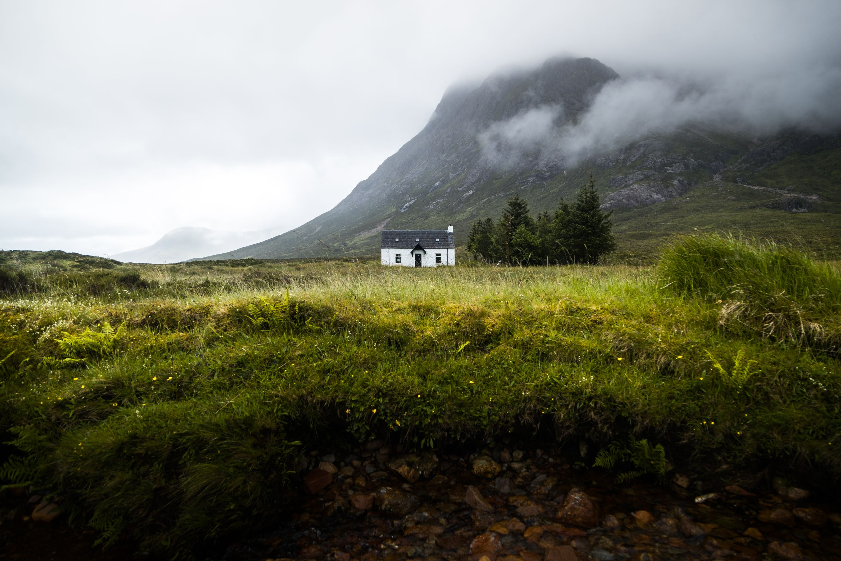 A lone house set amongst grassy field and mountain.