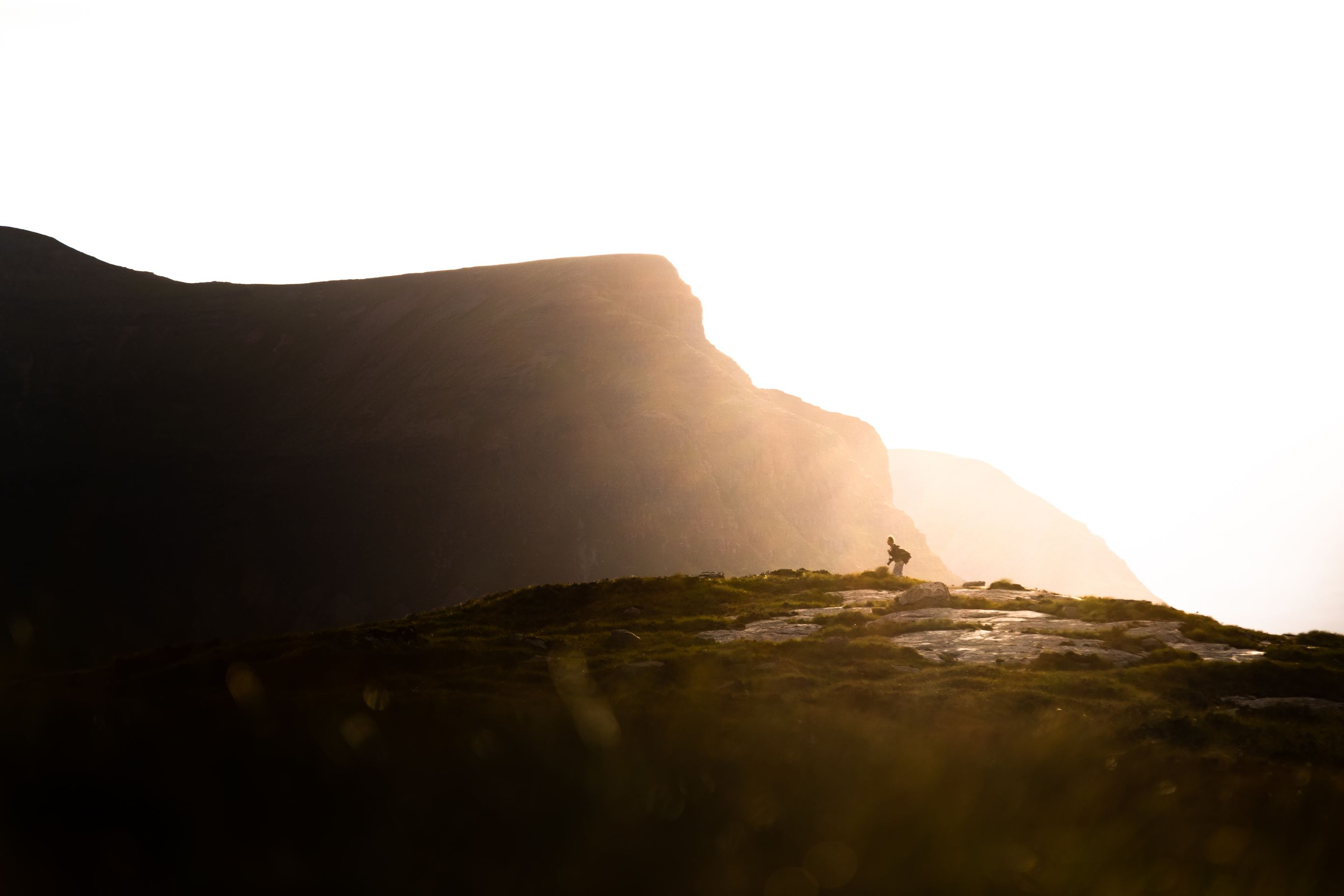 Man walking across rocks with a mountain in the background.