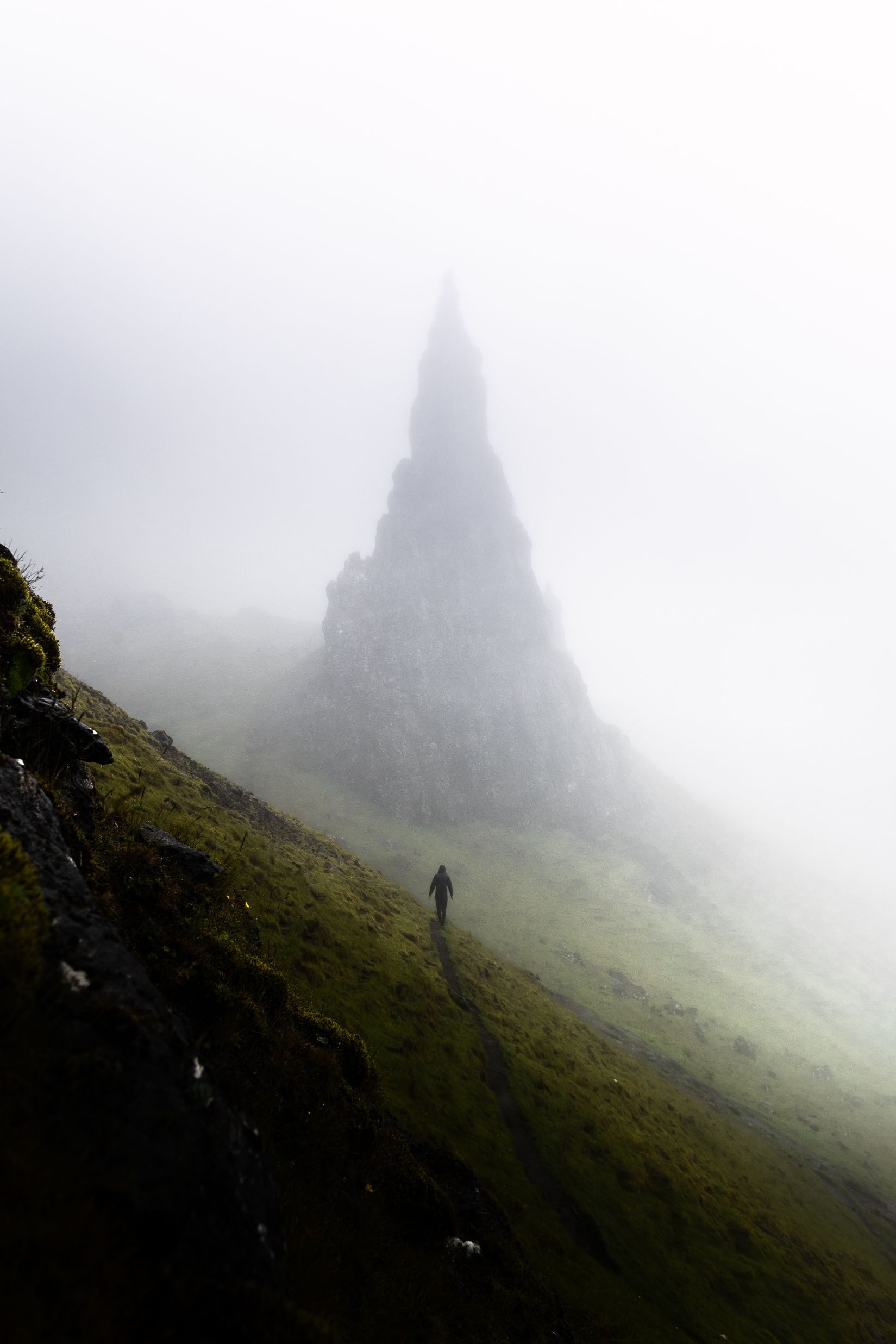 A figure walking in the mist towards rocky peak.